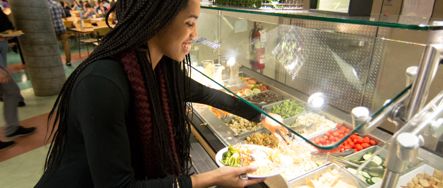 Student selecting food from buffet