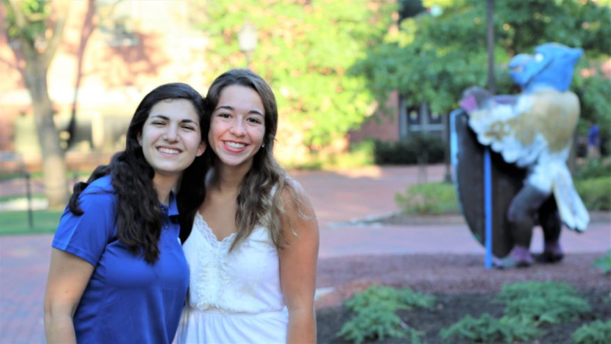 Two students on move-in day with arms wrapped around each other, heads pressed together.