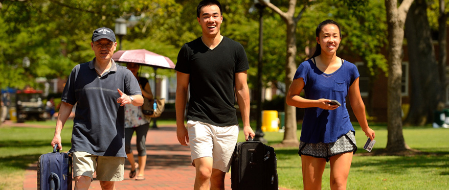 Student walking across campus with luggage