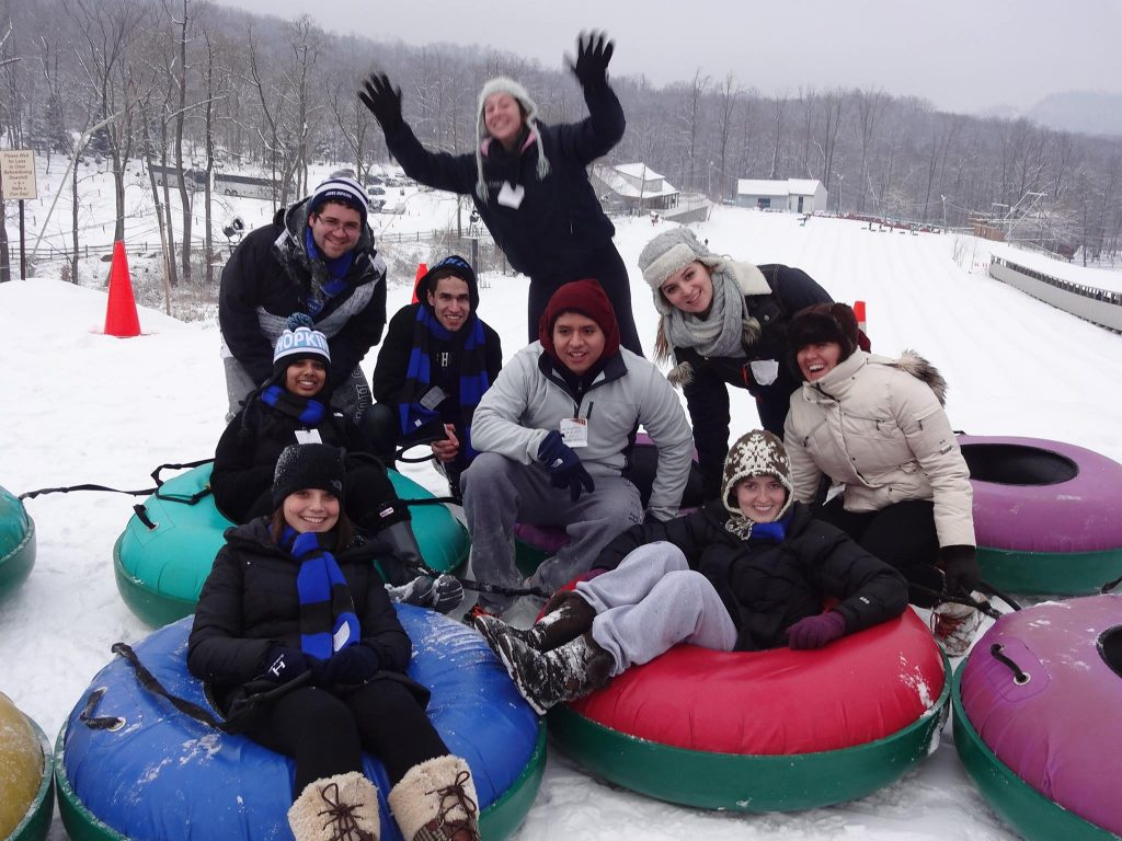 students on a mountain with snow tubes