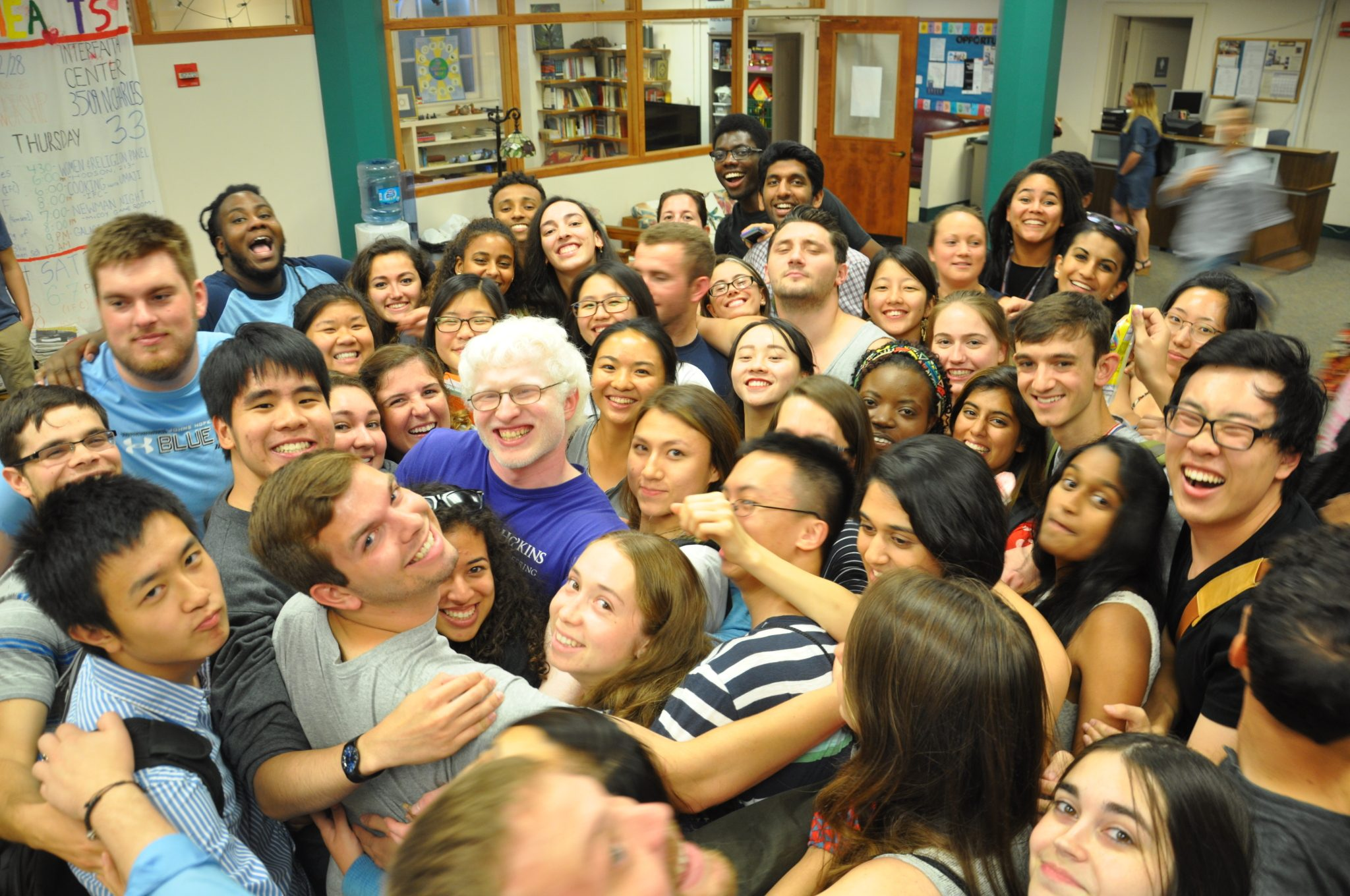 Students and faculty embracing in a group hug