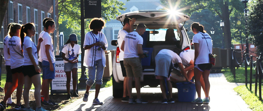Student volunteers help a student move into their dorm