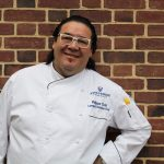 Chef Chin smiling against brick wall
