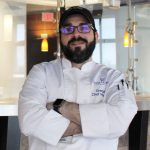 Chef Perez smiling with arms crossed