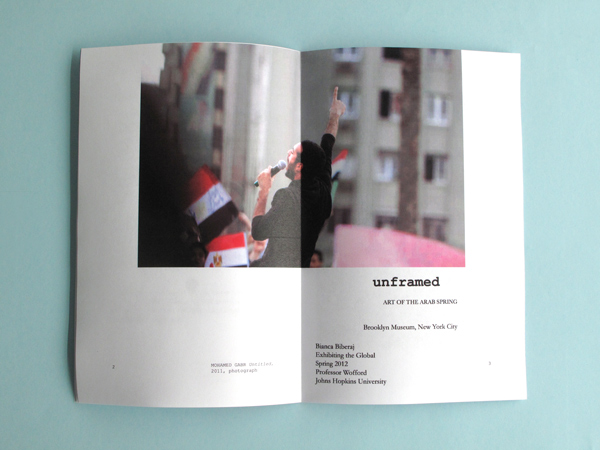 """The catalog has been opened to reveal a full size page of a man outside speaking into a microphone with the title """"unframed""""."""