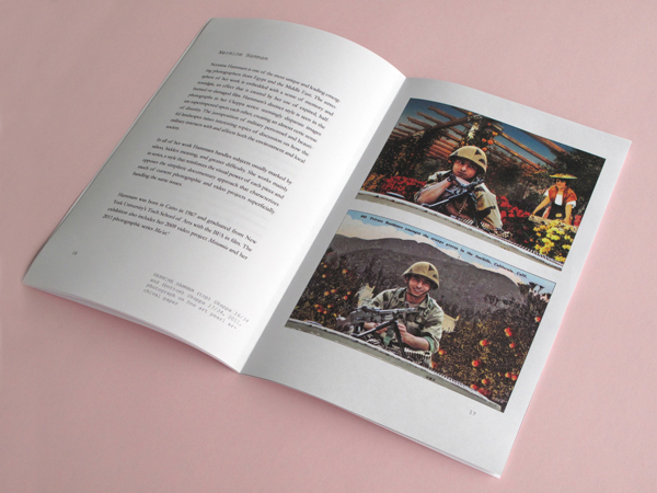 The catalog has been opened to a page with two separate images of military personnel in uniform with weapons and three paragraphs of text on the other page.