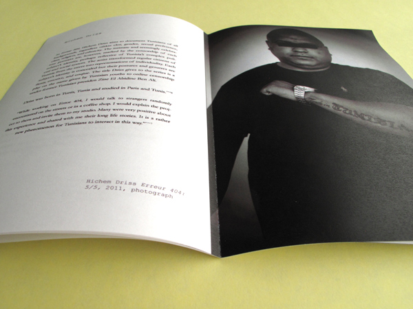 The catalog has been opened to a page with an image of a man bearing a tattoo across his arm and two paragraph texts on the other page.