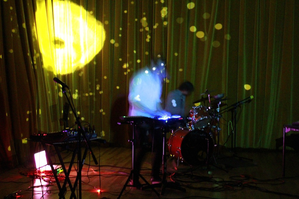 A blurred image of a person, performing on keyboard with electronics beside them and a drummer on stage.