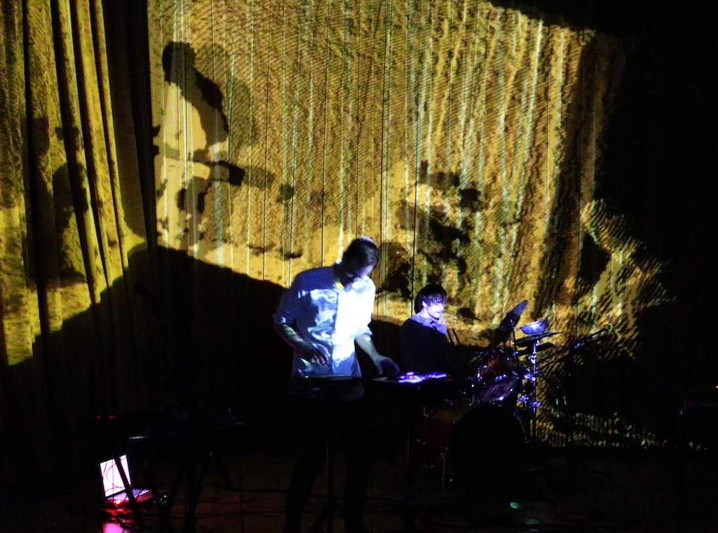 An overhead view of a man on keyboard and a drummer on a dark stage.