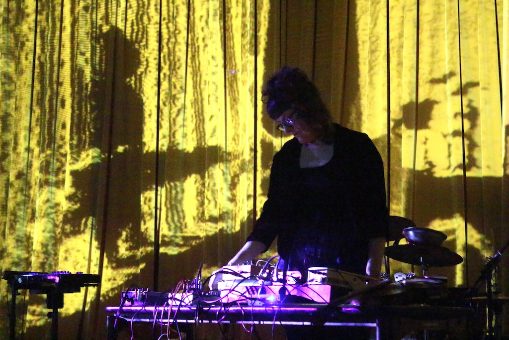 A dark-lit person with musical electronics performs on stage.