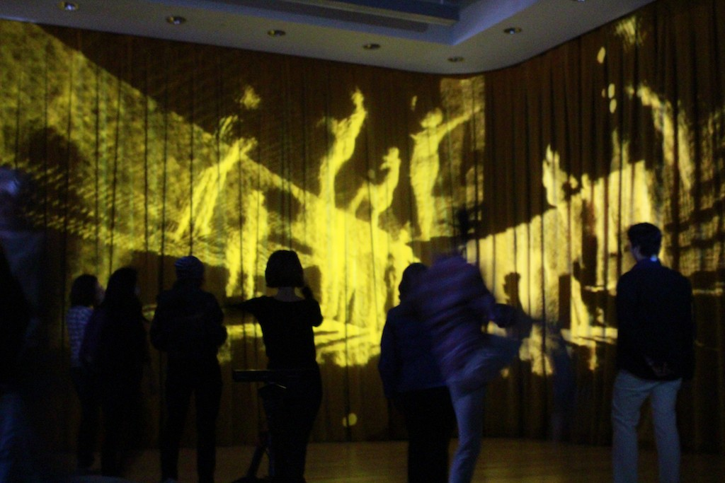 In a dark lit room, the silhouette of people dancing in front of a stage.