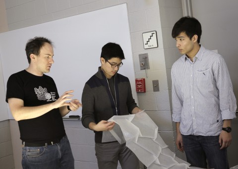 Three individuals on the Origami Cosmic Web team talk while examining folded tracing paper