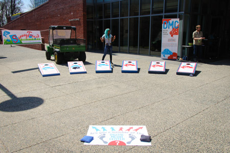 Outdoor shot of DMC SurveyToss‽ in Mattin Center courtyard with six cornhole boards, starting point, bean bags and banners in background