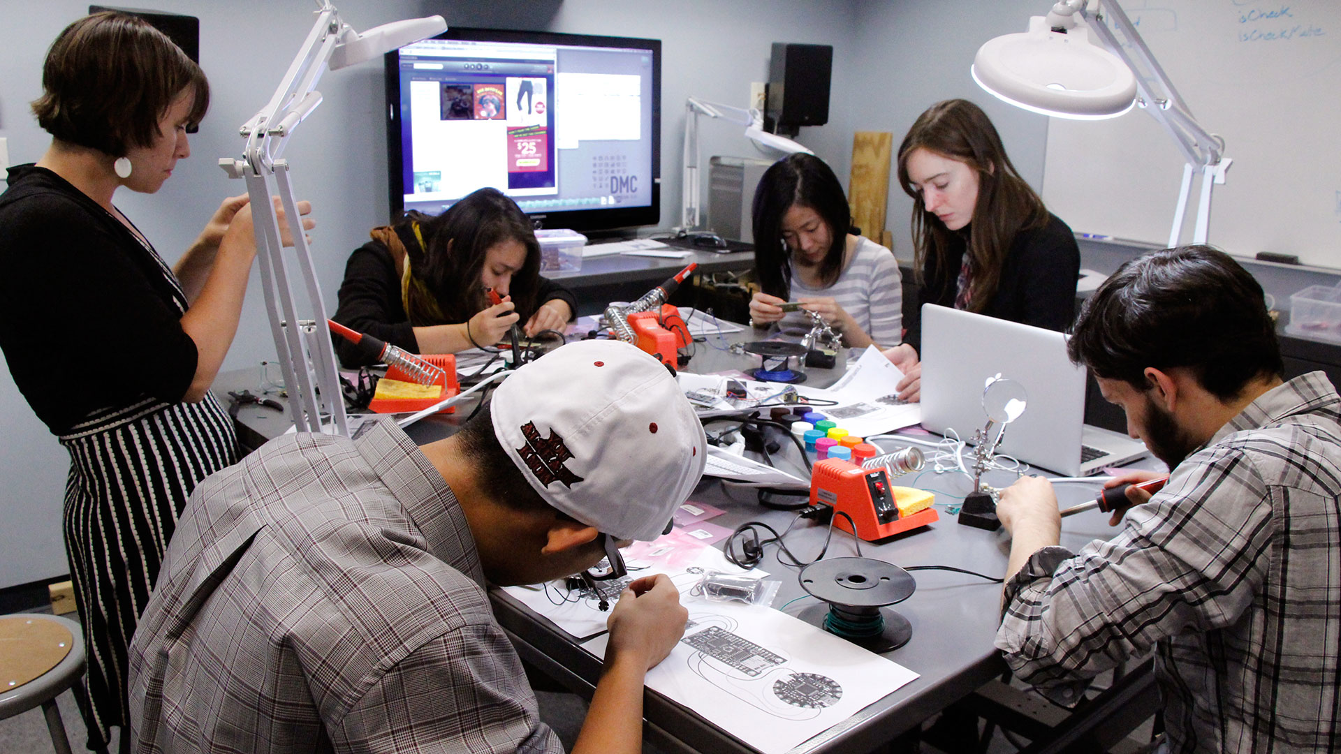 Group of students crowded around workbench for a DMC Makerspace Workshop