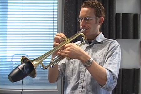 A man playing a trumpet in a casual, unknown space.