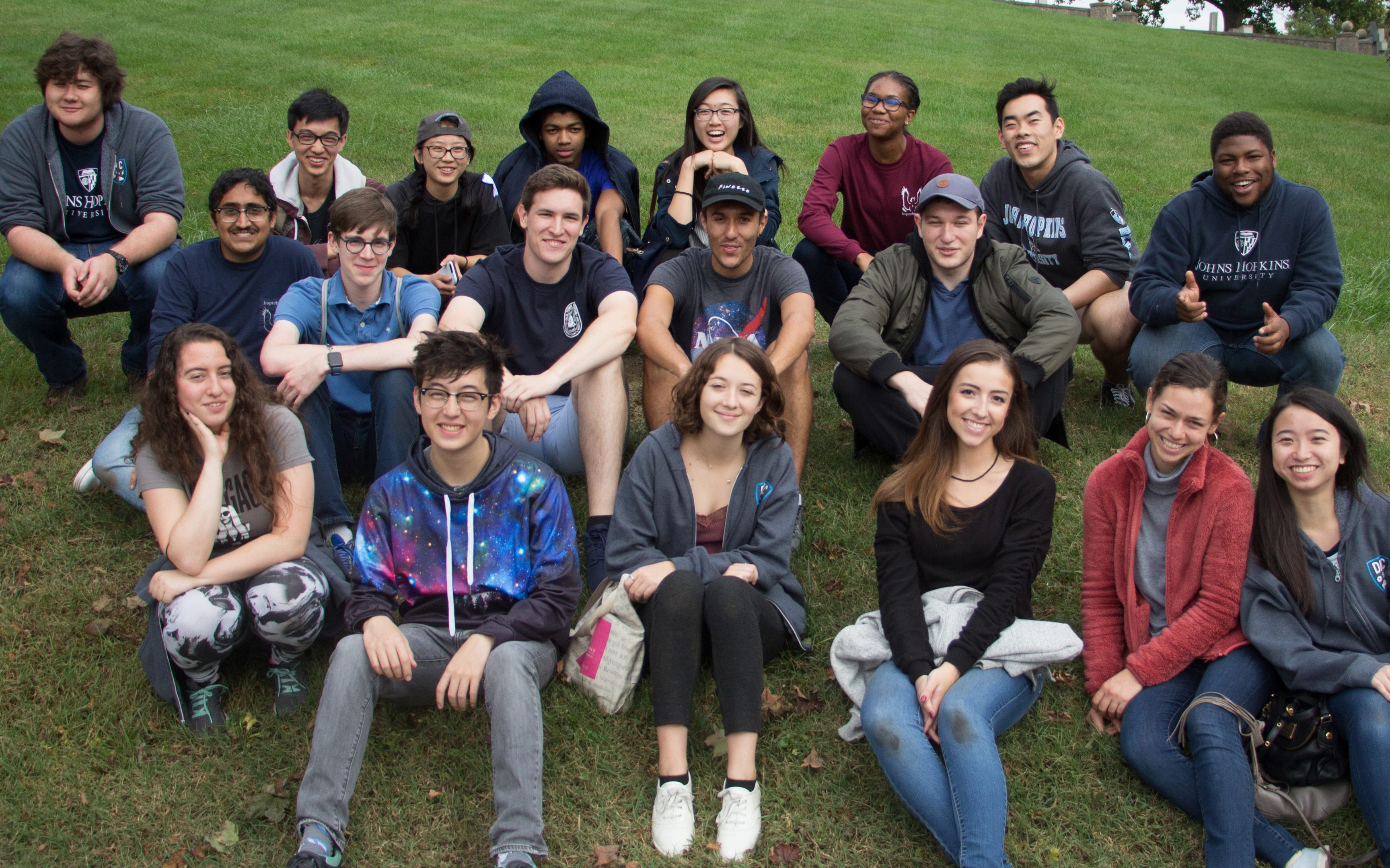 A group of students sit on the lawn and smile for a picture.