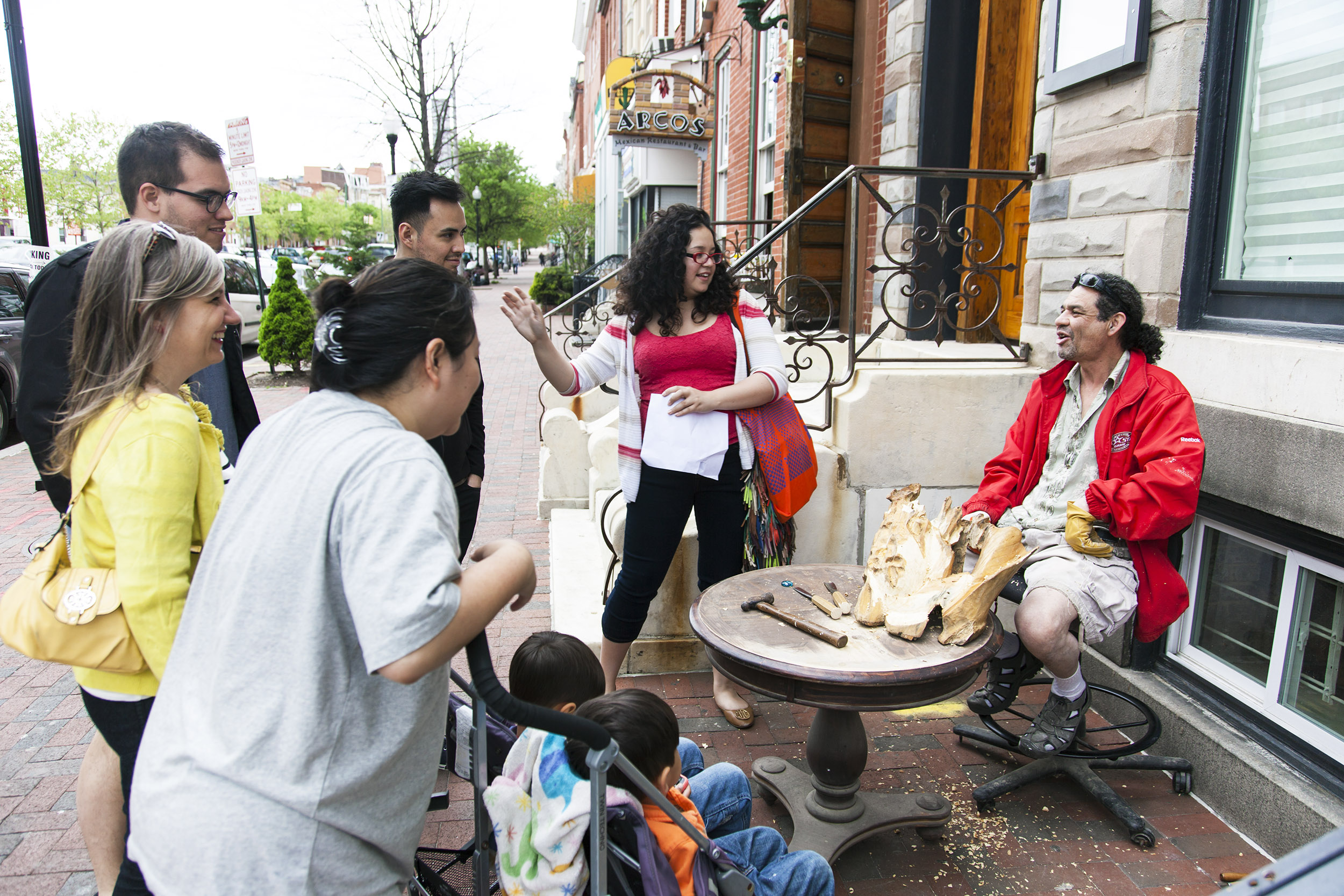Curator Michelle Gomez talks with neighbors during Devociones y Fe neighborhood walk