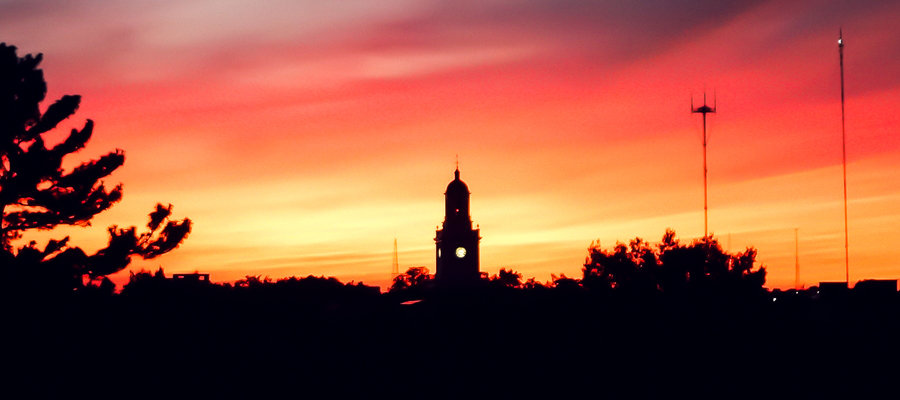A silhouette of Gilman Hall during sunset with a brilliantly lit red, orange, and yellow background colors in the sunset.