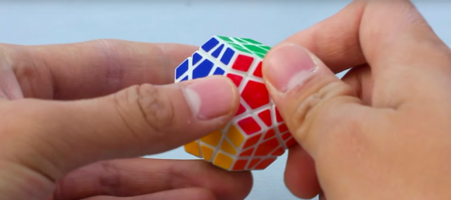 An extreme close-up of hands holding a twisty puzzle.