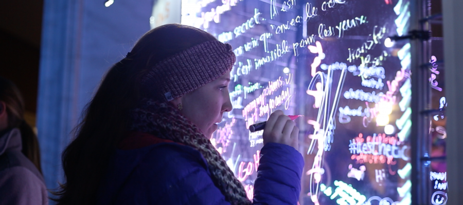 A student in a coat, scarf, and hat writes on an illuminated glass with glow in the dark ink.
