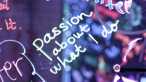 """An extreme close up of """"Passion about what I do"""" written on an acrylic panel in neon marker."""