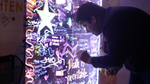 A student writes on an acrylic panel covered in neon writing.