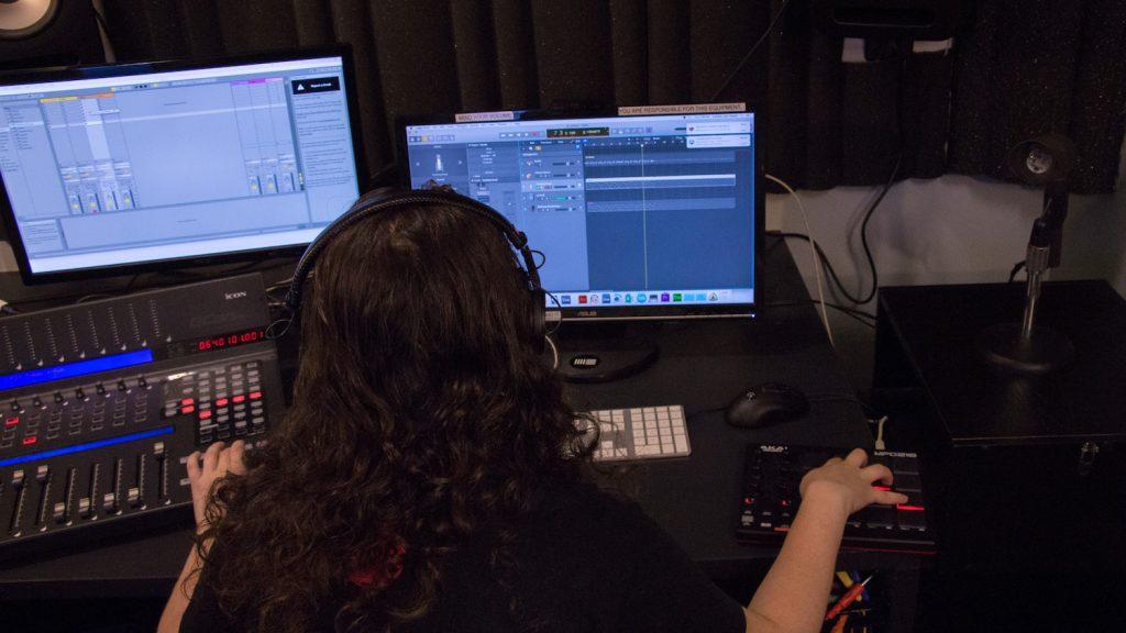 Student creating music in the audio studio