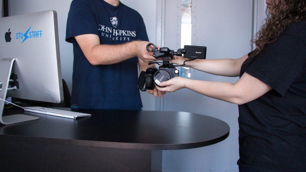 DMC staff member handing student a piece of camera equipment.