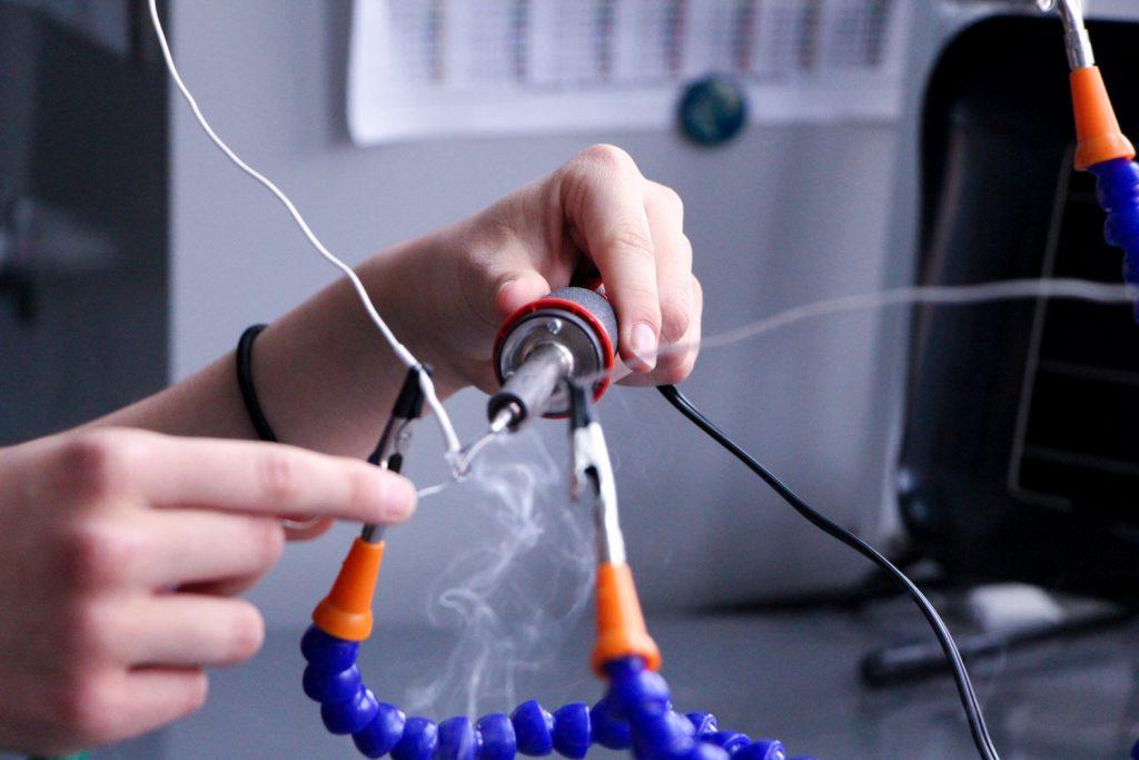 Student soldering equipment in Maker space