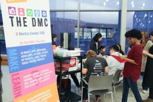 Students sitting at a round table working on their crafts, a DMC sign highlighting the event in the foreground.