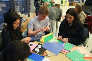 Three students at a table with colored construction paper around them while they craft with paper.