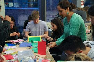 Multiple individuals working at a table with construction paper and craft supplies around the table.