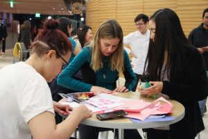 Three female students work on their individual paper cards.
