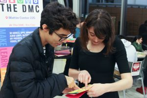 Two students huddle together looking at a handmade card.