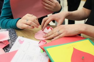 An extreme close-up of hands crafting colored paper into the shape of a heart.