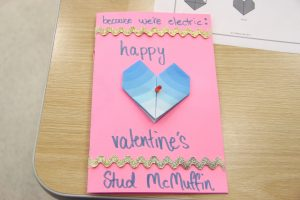 """A handmade card that reads, """"because we're electric: happy valentine's Stud McMuffin""""."""