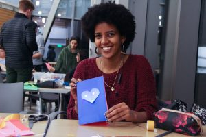 A woman shows off her handmade card that is blue with a heart on the front.