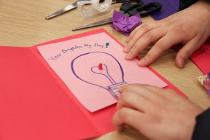 """An extreme close-up of hands assembling a handmade paper card that shows a light bulb and """"You Brighten My Day!"""""""