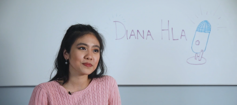 Diana Hla sits in front of a whiteboard with a soft smile and stares into the distance.