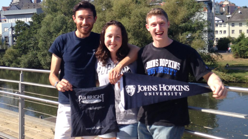 Adam Tabeling, Arielle Kaden, and Yitzhak Snow standing on a bridge in Germany, holding Hopkins and Fulbright gear