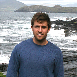 Mark standing in front of the ocean with waves crashing on rocks.