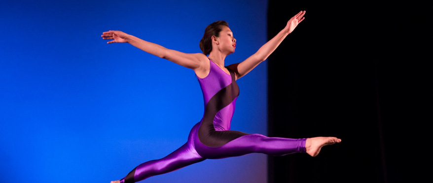 A single dancer leaps across the stage in a purple leotard.