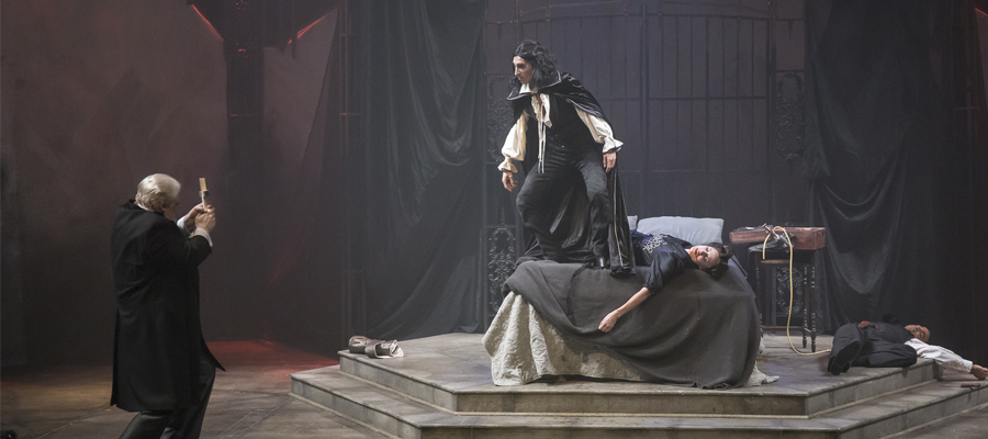 Dracula stands over his victim while a man bravely holds up a cross to defend himself.