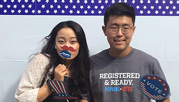2 JHU students with Hopkins Votes signs