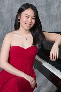 Stephanie Cai sitting in front of a piano.