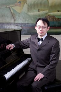 A head shot of Mengyu Lan sitting at a piano.