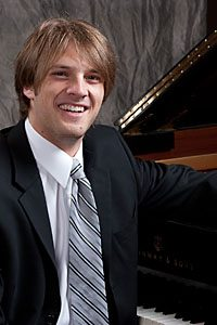 A head shot of Matthew Lochner sitting at a piano.