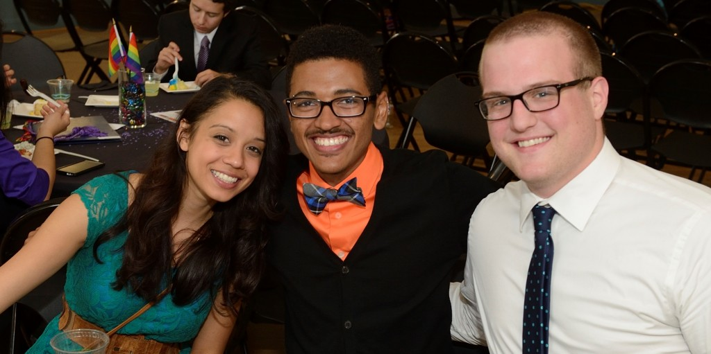 Three well dressed students get close together, with big smiles, while sitting at a table.