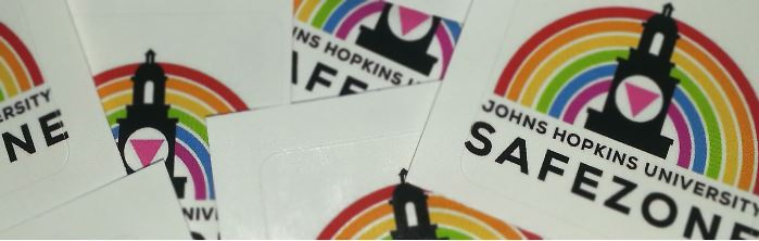 "A close up of a pile of stickers that read, ""SafeZone""."