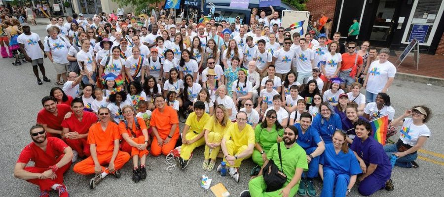 A large group of people sitting together wearing matching Pride shirts while a few individuals in the foreground wearing solid color scrubs that as a group depict the rainbow colors.